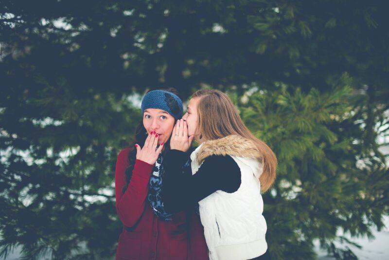 唇に手を当てながら女性の耳にささやく女性